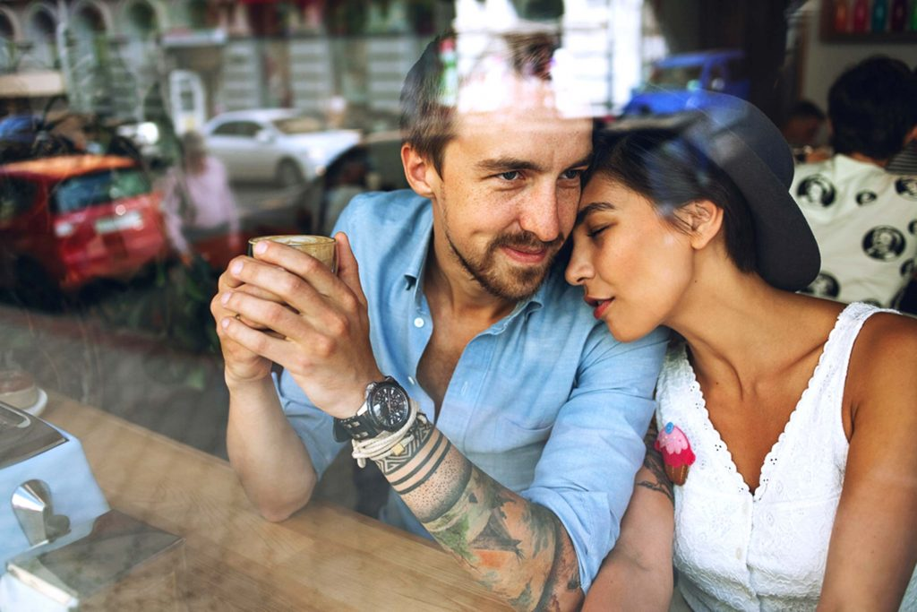 Couple after building intimacy in a relationship in a coffee shop snuggling unaware of the outside world