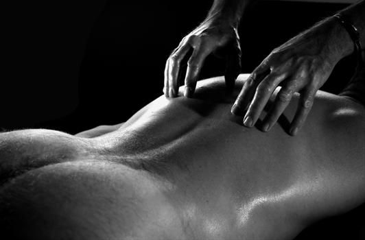 man's back and naked bum having massage from woman
