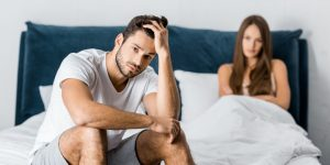 Man sitting away from wife in bed due to premature ejaculatory dysfunction